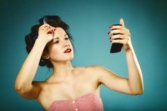 Девушка в curlers вводя волосы в моду смотря в зеркале Стоковые Изображения RF