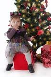 Девушка в fairy костюме сидя под рождественской елкой Стоковые Изображения