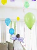 Девушка в Fairy крылах при воздушные шары взбираясь на софе Стоковая Фотография RF