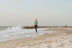Девушка в sportswear бежать вдоль линии прибоя над красивейшими облаками птиц цветы раньше летают море подъемов отражения природы Стоковое Изображение