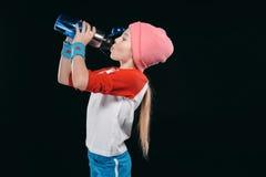 Девушка в sportswear выпивая от бутылки спорта изолированной на черноте Стоковое Изображение