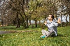Девушка в sportswear делая йогу в природе стоковое изображение