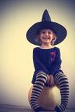 ДЕВУШКА в witch& x27; тыква шляпы s Стоковое Изображение
