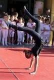 Девушка гимнастики стоя на ее кулаках на общественном этапе Стоковые Изображения RF