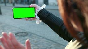Девушка говорит на смартфоне greenscreen телефона Развевает рука к людям которые они видят на экране видеоматериал