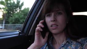 Девушка говорит по телефону и управляет на автомобиле на дороге города с открытым окном видеоматериал