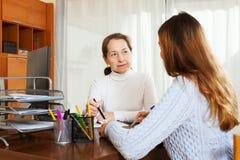 Девушка говоря к работнику с компьютером стоковая фотография rf