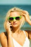 Девушка говоря на мобильном телефоне на пляже Стоковое Фото