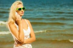 Девушка говоря на мобильном телефоне на пляже Стоковые Фото