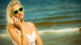 Девушка говоря на мобильном телефоне на пляже Стоковые Изображения