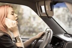 Девушка говоря на мобильном телефоне пока управляющ автомобилем Стоковая Фотография