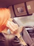 Девушка говоря на мобильном телефоне пока управляющ автомобилем Стоковое Изображение