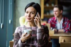 Девушка говоря на телефоне Кофе девушки выпивая в кафе Стоковые Фото