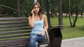 Девушка говоря на smartphone в парке города женщина сидя на стенде с устройствами в парке видеоматериал