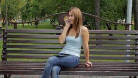 Девушка говоря на smartphone в парке города женщина сидя на стенде с устройствами в парке сток-видео