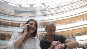 Девушка говоря по телефону, и пункты парня с часами на предпосылке фонтана в торговом центре акции видеоматериалы