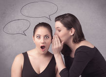Девушка говоря секретные вещи к ее подруге Стоковая Фотография