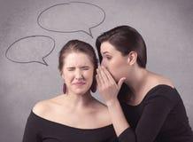 Девушка говоря секретные вещи к ее подруге Стоковое фото RF