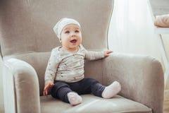 девушка 1 года нося стильные одежды, сидя в винтажном стуле в комнате Стоковые Изображения