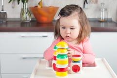 Девушка 2 года старого при длинные волосы играя с дизайнерской конструкцией дома, строящ башни, сконцентрировала ход Стоковые Изображения RF
