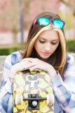 Девушка городского портрета красивая при скейтборд смотря вниз стоковое изображение
