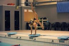 Девушка готовая для того чтобы поскакать в бассейн крытого спорта стоять на оружиях с ногами вверх стоковые фотографии rf