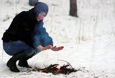 Девушка греет его руки над огнем в зиме Стоковая Фотография RF