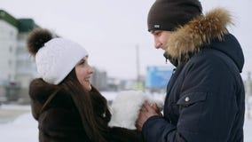 Девушка греет руки парня Прогулка зимы молодой пары в любов сток-видео