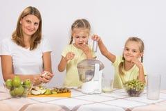 Девушка грызет груши до тех пор пока мама и сестра не сжимают сок в juicer Стоковые Фото