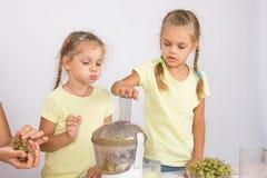 Девушка грызет груши до тех пор пока мама и сестра не сжимают сок в juicer Стоковые Изображения