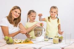 Девушка грызет груши до тех пор пока мама и сестра не сжимают сок в juicer Стоковые Фотографии RF