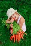 Девушка грызет морковь с пуком морковей Стоковые Изображения RF