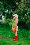 Девушка грызет морковь с пуком морковей Стоковое Фото