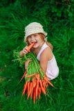 Девушка грызет морковь с пуком морковей Стоковые Фотографии RF