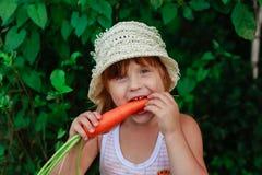 Девушка грызет морковь Стоковое Изображение