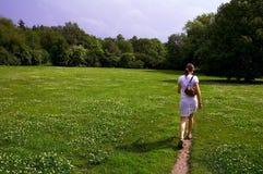 Девушка гуляя через лужок стоковая фотография rf
