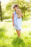 Девушка гуляя через плюшевый медвежонка нося поля Стоковое фото RF