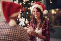 Девушка дает подарок рождества к его парню Стоковая Фотография RF