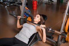 Девушка делает жим лёжа в тренировке мышц рук и рук Стоковые Изображения