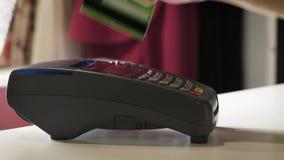 Девушка делает приобретение с банком или кредитную карточку используя магнитную ленту акции видеоматериалы