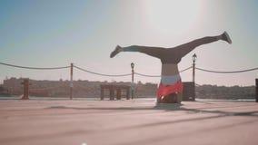 Девушка делает Headstand на заходе солнца около моря акции видеоматериалы