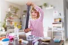 Девушка делая домодельную игрушку шлама стоковое фото rf