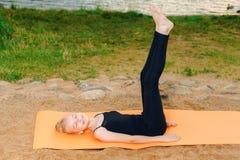 Девушка делая йогу на заходе солнца rive стоковая фотография rf