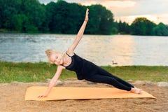 Девушка делая йогу на заходе солнца rive стоковые фотографии rf