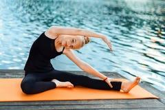 Девушка делая йогу на заходе солнца rive стоковые фото