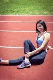 Девушка делая протягивающ тренировки на следе Стоковое Изображение