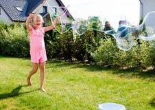 Девушка делая пузыри мыла в домашнем саде Стоковые Изображения RF