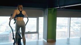 Девушка делая разминку на orbitrek в спортзале сток-видео