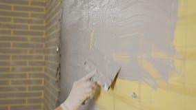 Девушка делая ремонты в квартире Женщина управляет шпателем на бетонной стене Ремонтировать квартиру Замазка  акции видеоматериалы