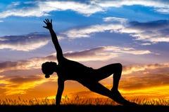 Девушка делая тренировки на заходе солнца Стоковое Фото